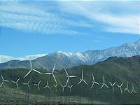 雪山の手前の砂漠に風車が並ぶ